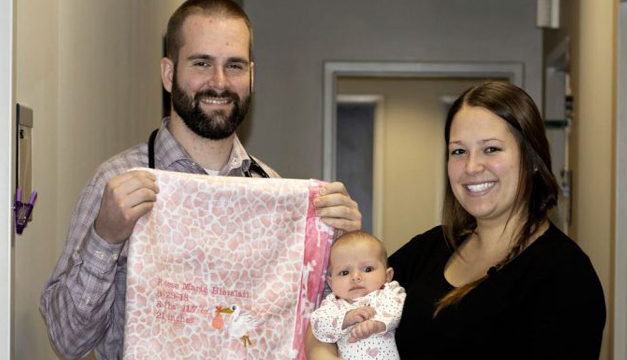 Un doctor cose mantas para arropar a cada bebé que ayuda a traer al mundo
